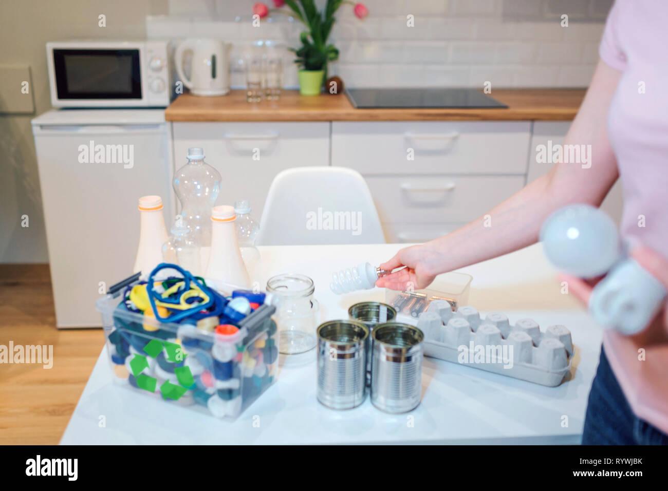 Reciclaje. Surtido de metal, plástico, vidrio, papel, residuos electrónicos sobre la mesa de la cocina Imagen De Stock