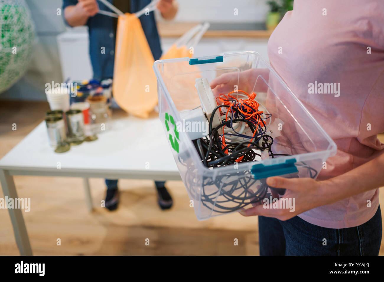 Concepto de reciclaje. Mezcla de residuos electrónicos en plástico contaner cerca. Mujer responsable es proteger el medio ambiente mientras que clasificar los residuos en casa Imagen De Stock