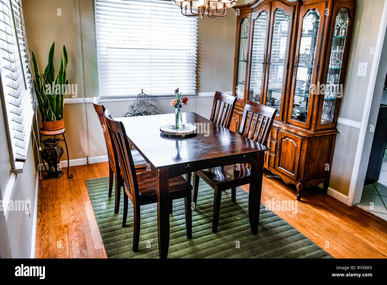 Una mesa de comedor y gabinete de china sobre un piso de madera con una alfombra verde. Serpiente de plantas y flores en la pantalla. Imagen De Stock