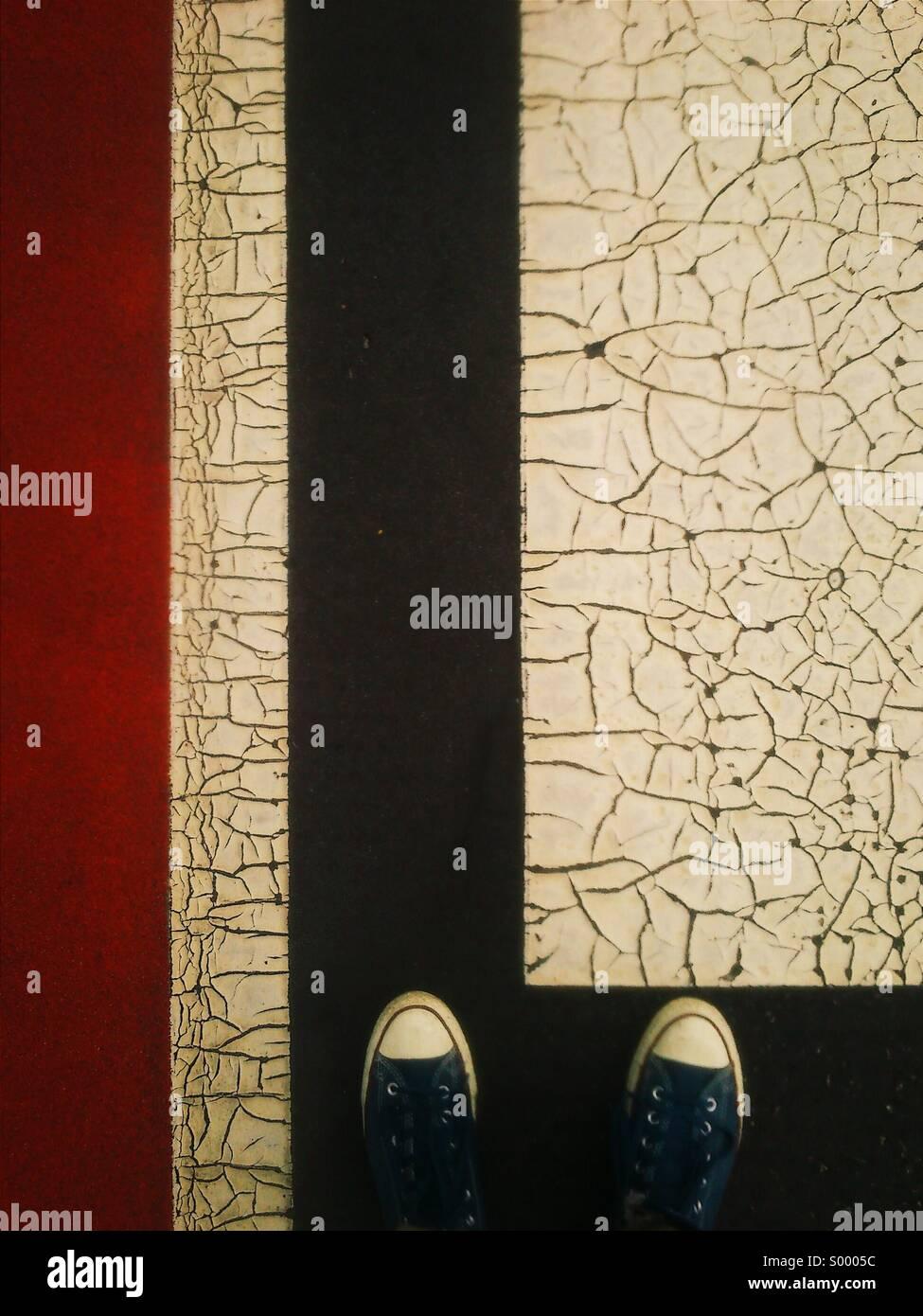 Mirando hacia los pies sobre la superficie pintada agrietado Imagen De Stock