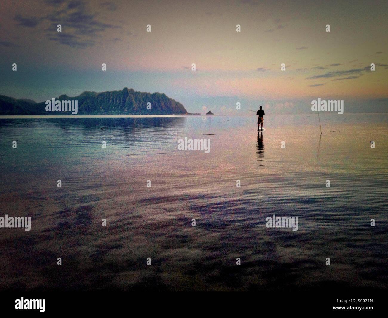Stand up junta de pesca en la bahía Kaneohe Bay, Oahu, Hawaii. Las montañas Koolau Kualoa como telón Imagen De Stock