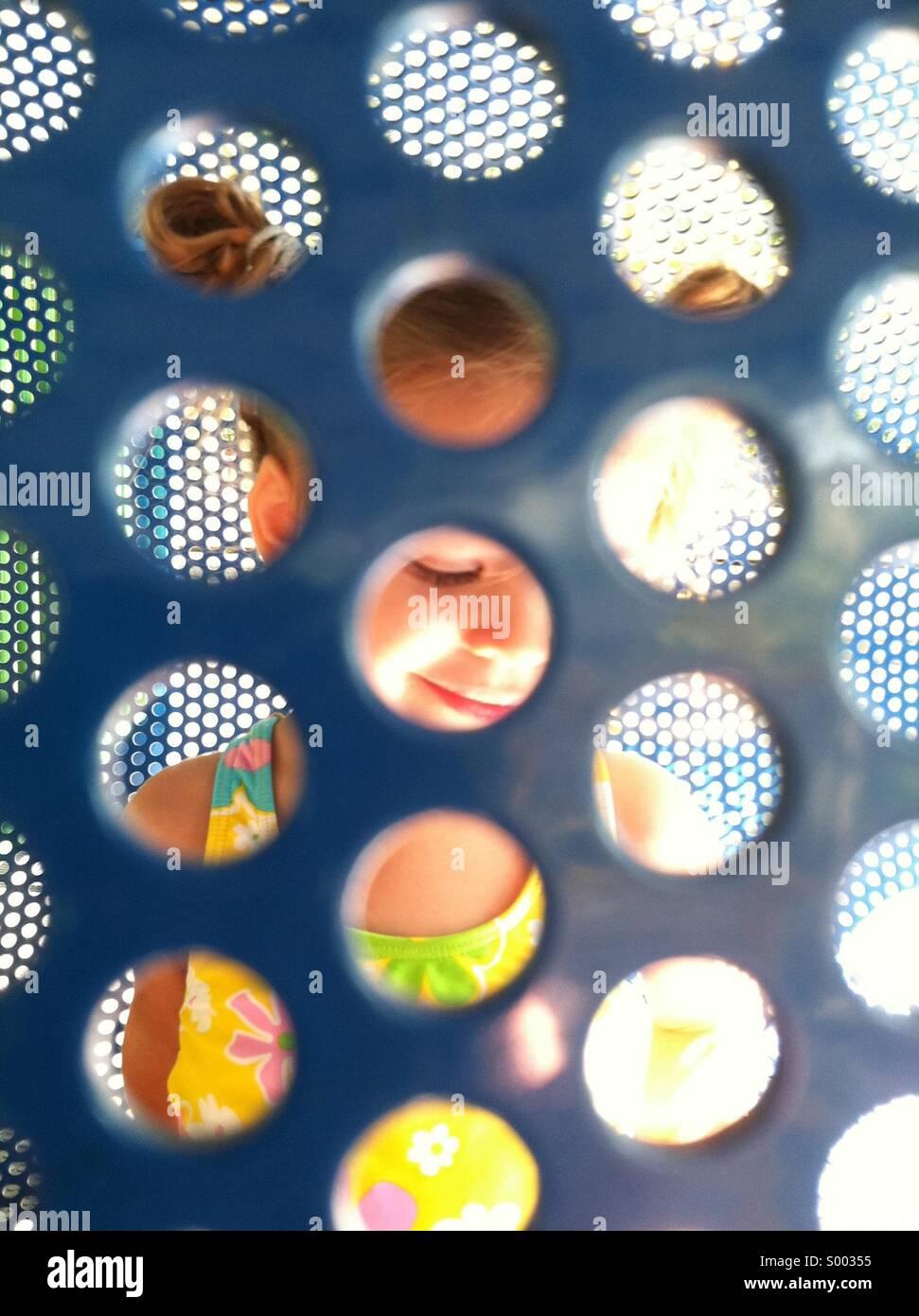 Una joven ve a través de una partición de recreo Imagen De Stock