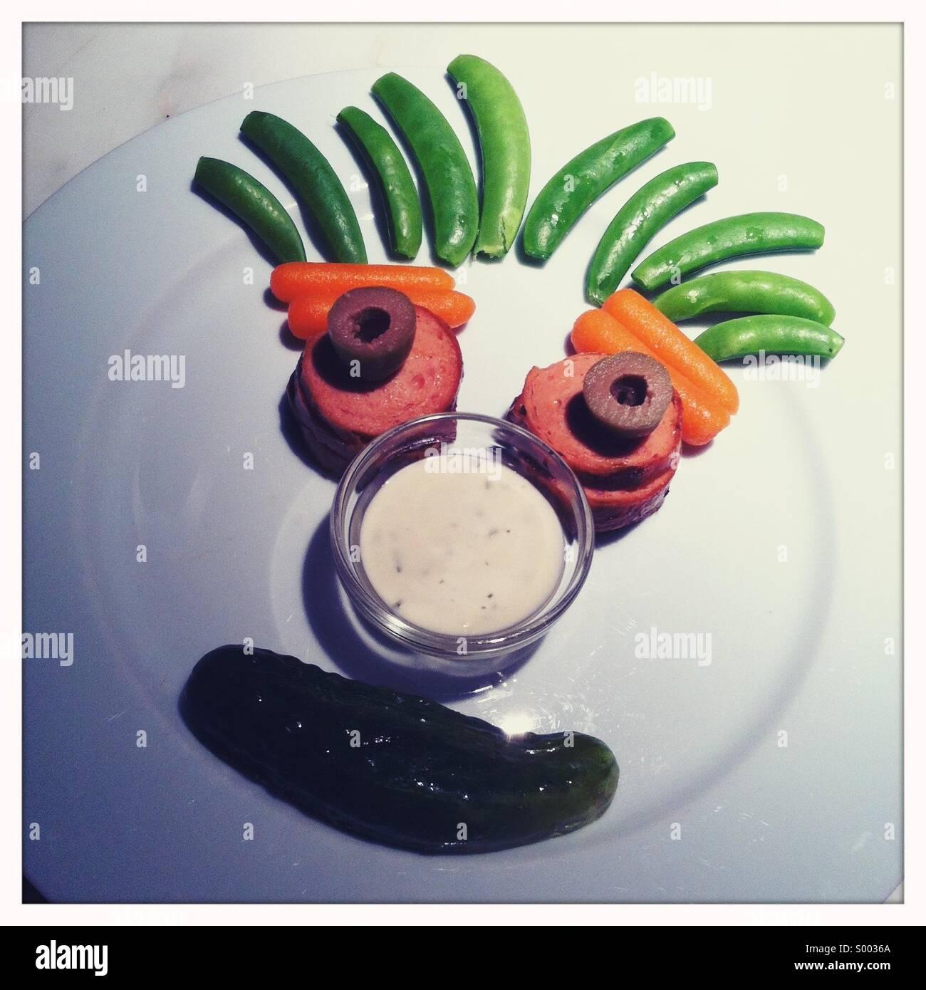 Un plato de comida del niño creado con una cara hecha a partir de los alimentos Imagen De Stock