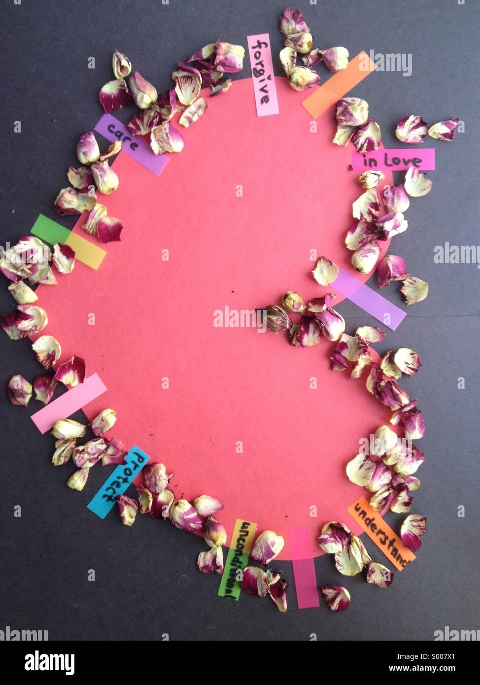 Corazón de papel con pétalos de rosas y pegatinas con palabras escritas Imagen De Stock