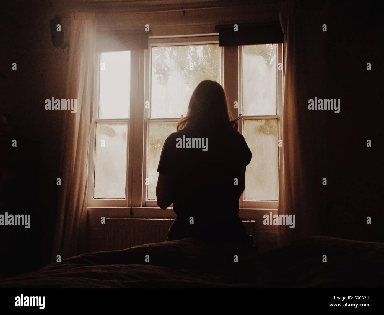 Una chica se prepara en su habitación al amanecer. Imagen De Stock
