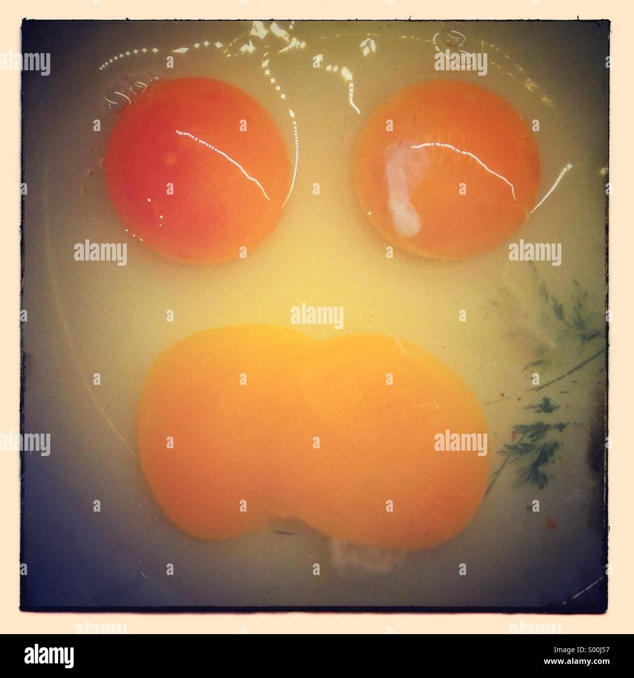 Cara de yema de huevos rotos. Caras en objetos Foto de stock