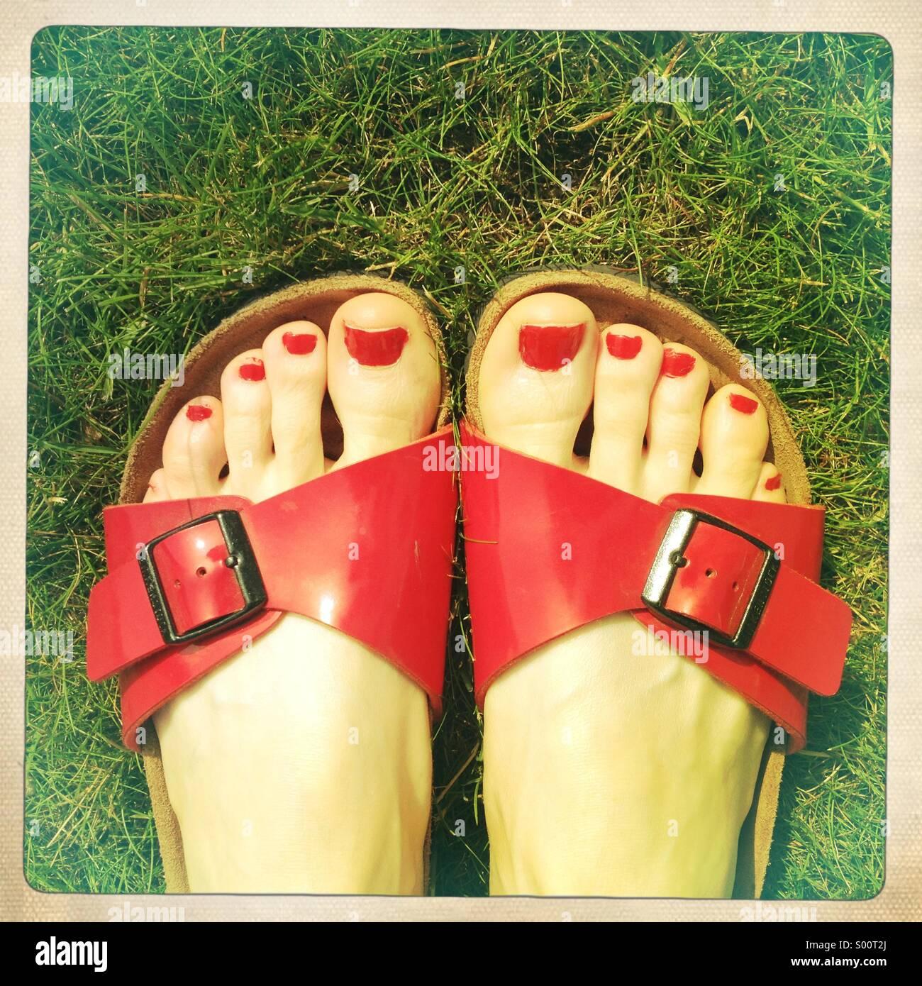 Dedos del pie pintados en sandalias sobre el césped Foto de stock