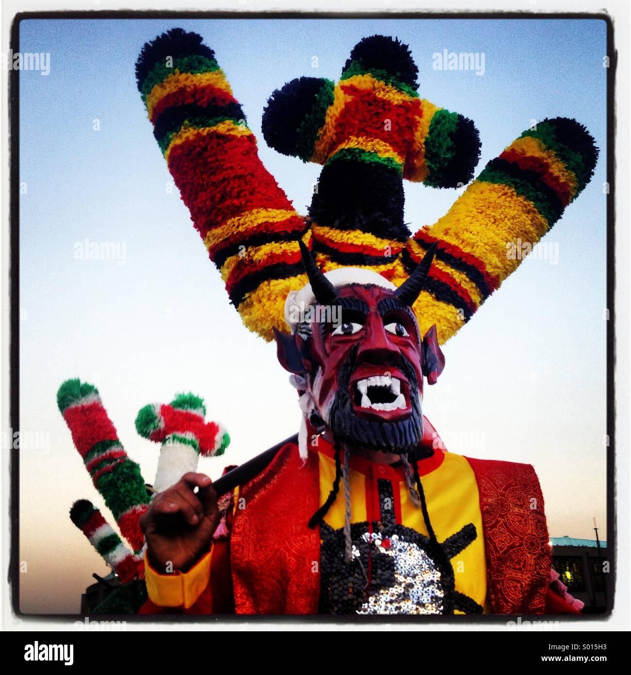 Un bailarín enmascarado disfrazado de diablo rojo realiza durante la peregrinación a la Basílica de Nuestra Señora Foto de stock