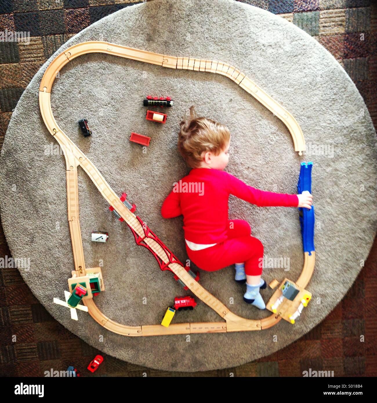 Niño jugando con un tren de juguete vía Imagen De Stock