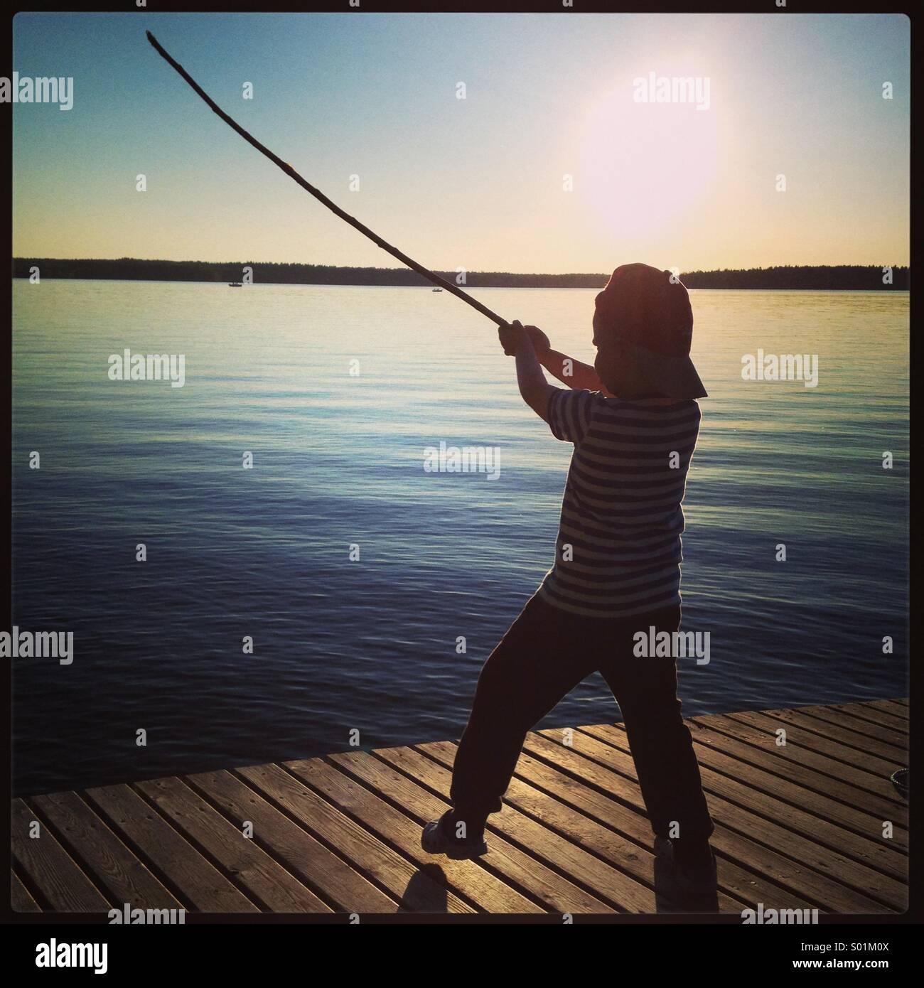 Un muchacho fingiendo ser un caballero Jedi espada luchador en un lago de vacaciones de verano Imagen De Stock