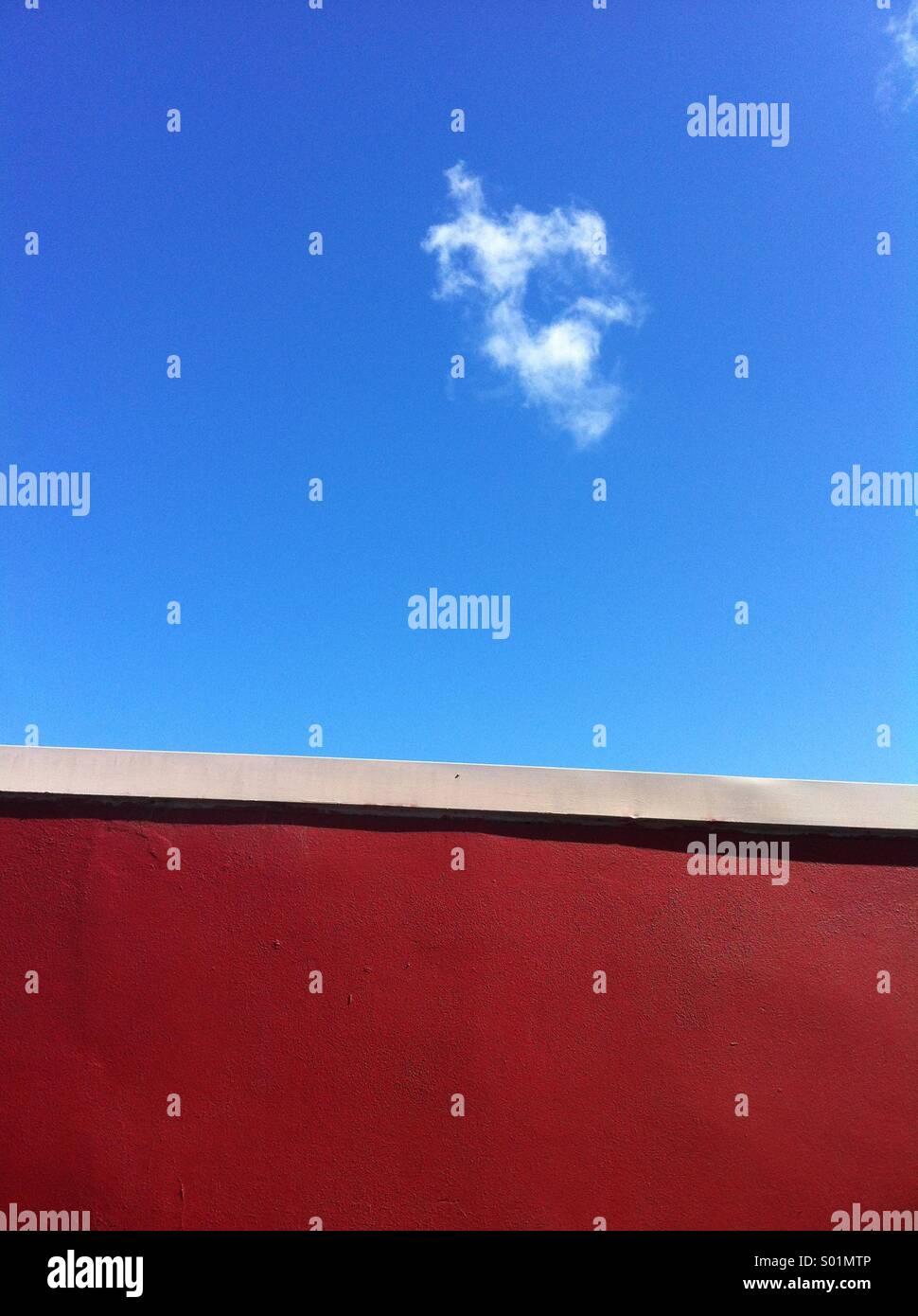 Pared roja y el cielo azul con nubes Imagen De Stock