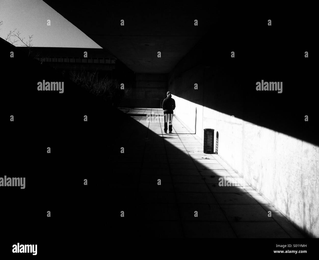 Una sola persona de pie en el pasaje de la luz Imagen De Stock