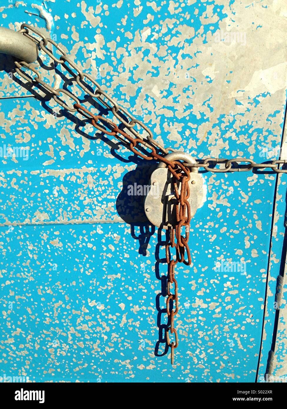El candado y la cadena papelera de reciclaje azul Foto de stock