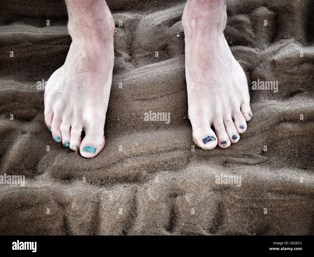 Un hombre de los pies descalzos en una playa de arena, vistiendo el ...