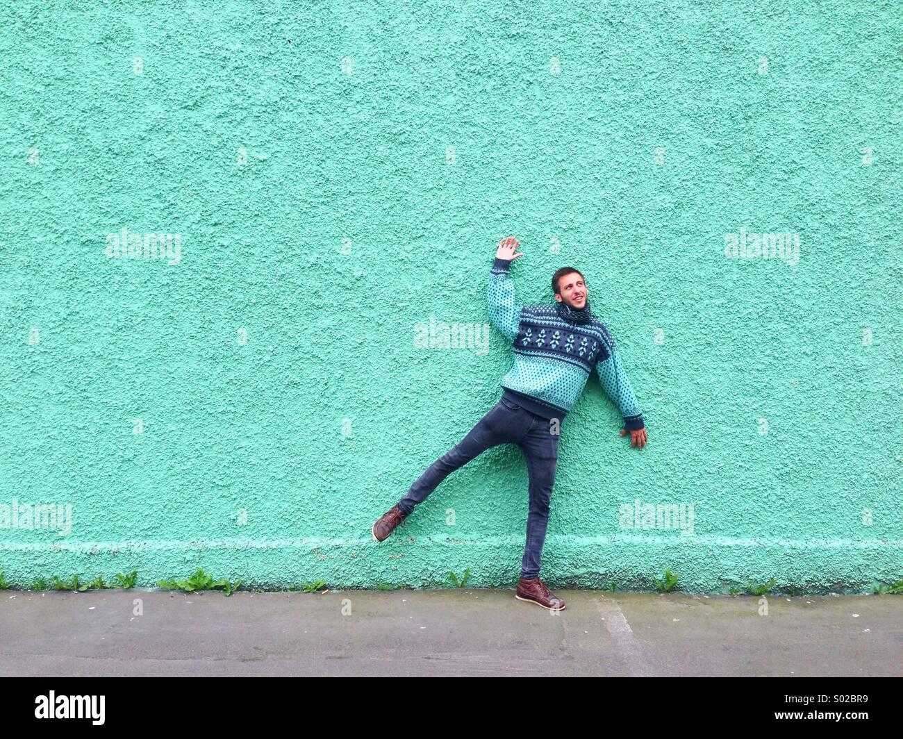 Hombre simulando que estaba atascado en una pared verde Imagen De Stock