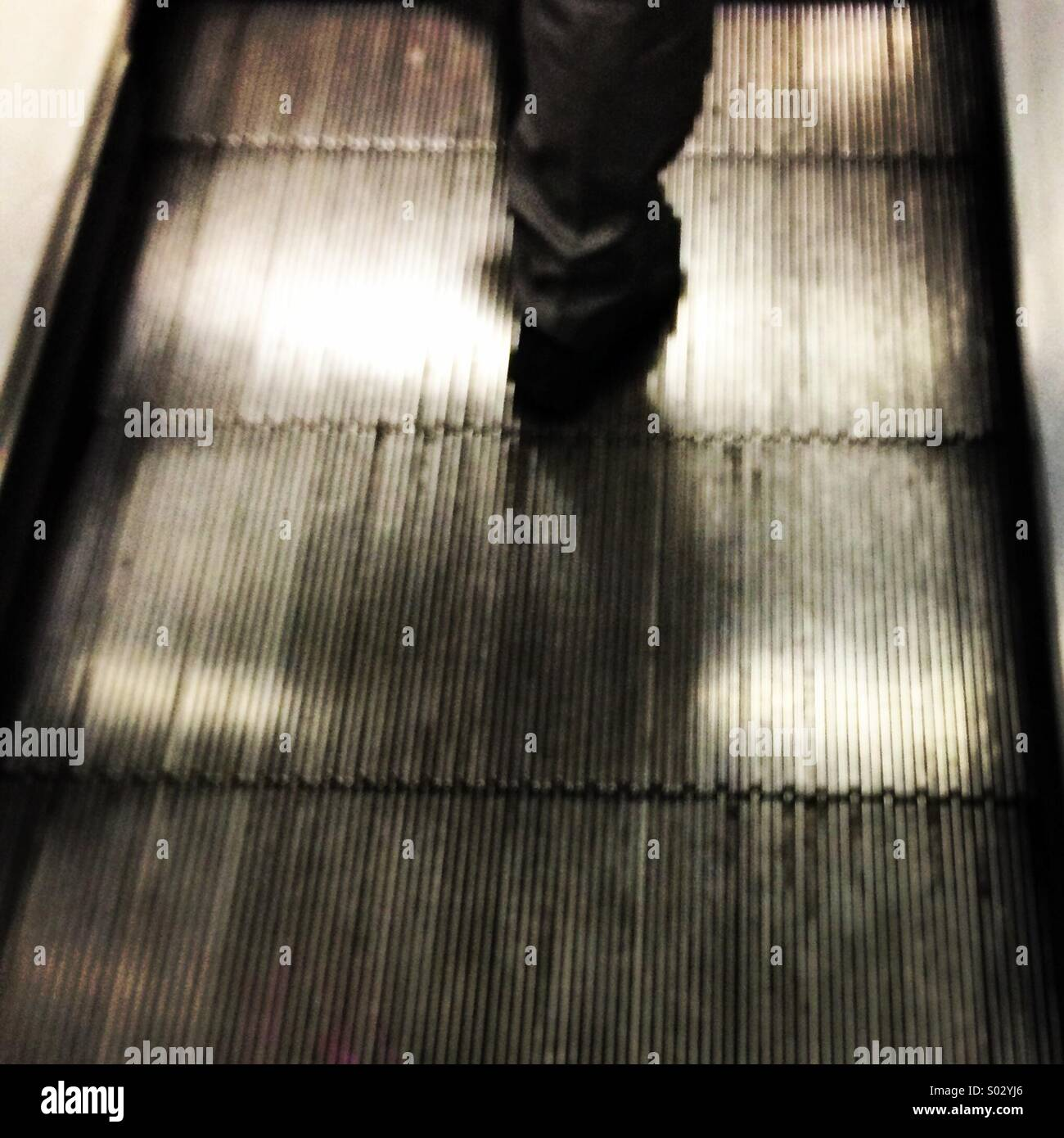 Piernas borrosa travelator caminando en una escalera mecánica. Imagen De Stock