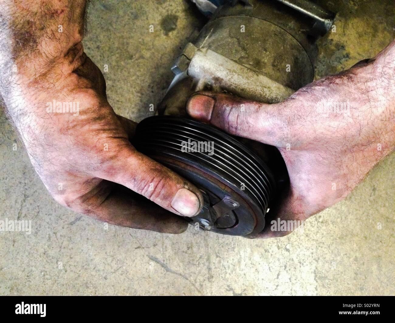 Manipulación de un mecánico de automóviles parte de aire acondicionado. Imagen De Stock