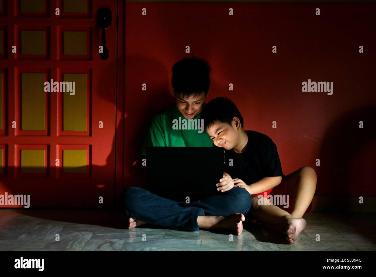 Jóvenes Niños Asiáticos, o hermanos con una computadora portátil en una sala vacía Imagen De Stock