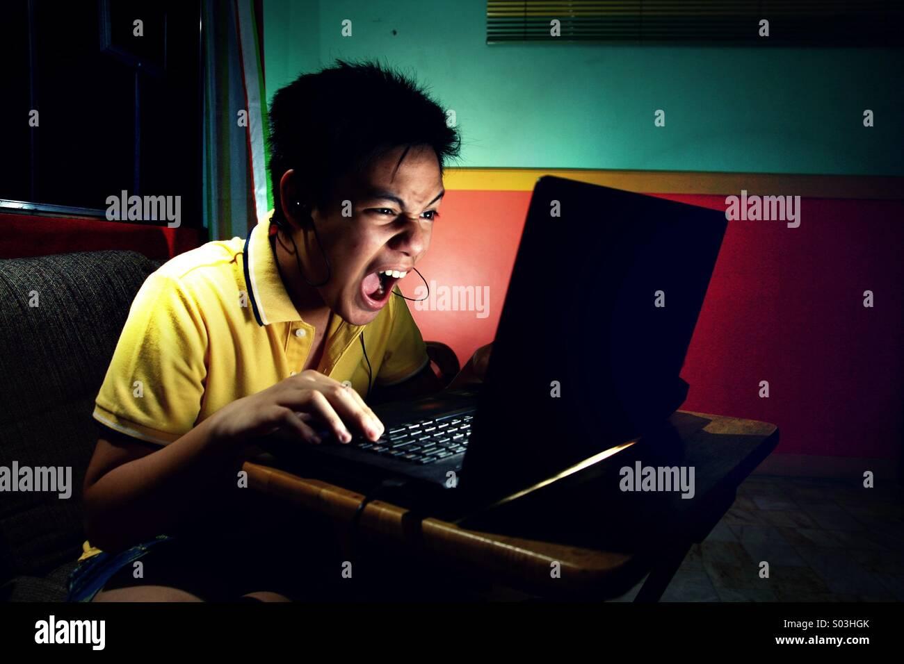 Jovencito asiático tocando intensamente en un ordenador portátil Imagen De Stock