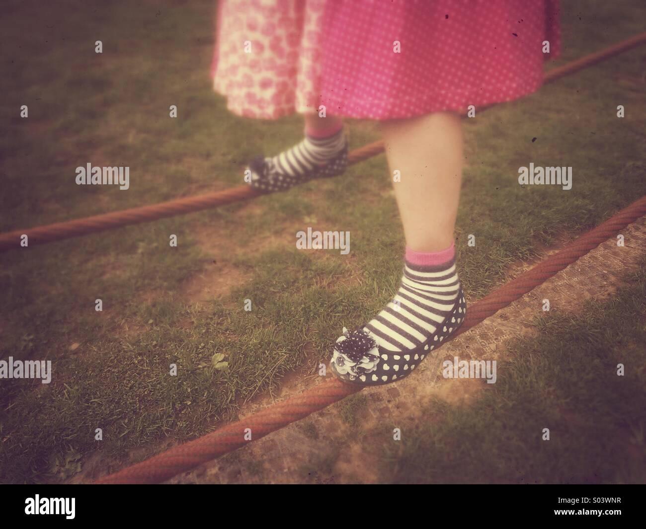 Los pies del joven equilibrio sobre cuerdas flojas. Imagen De Stock