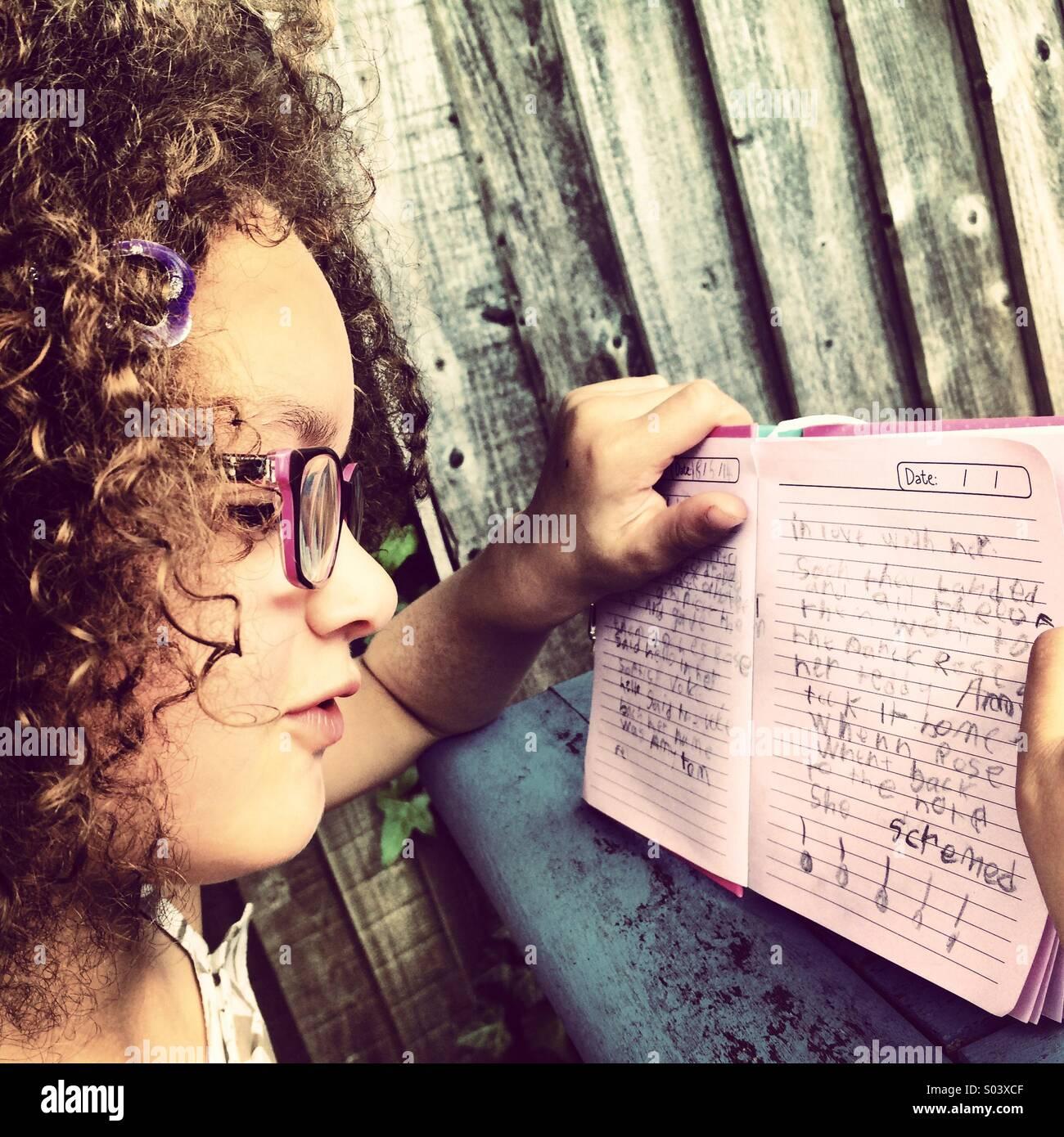 Pelo rizado de 6 años de edad, niña con gafas leyendo su diario. Imagen De Stock