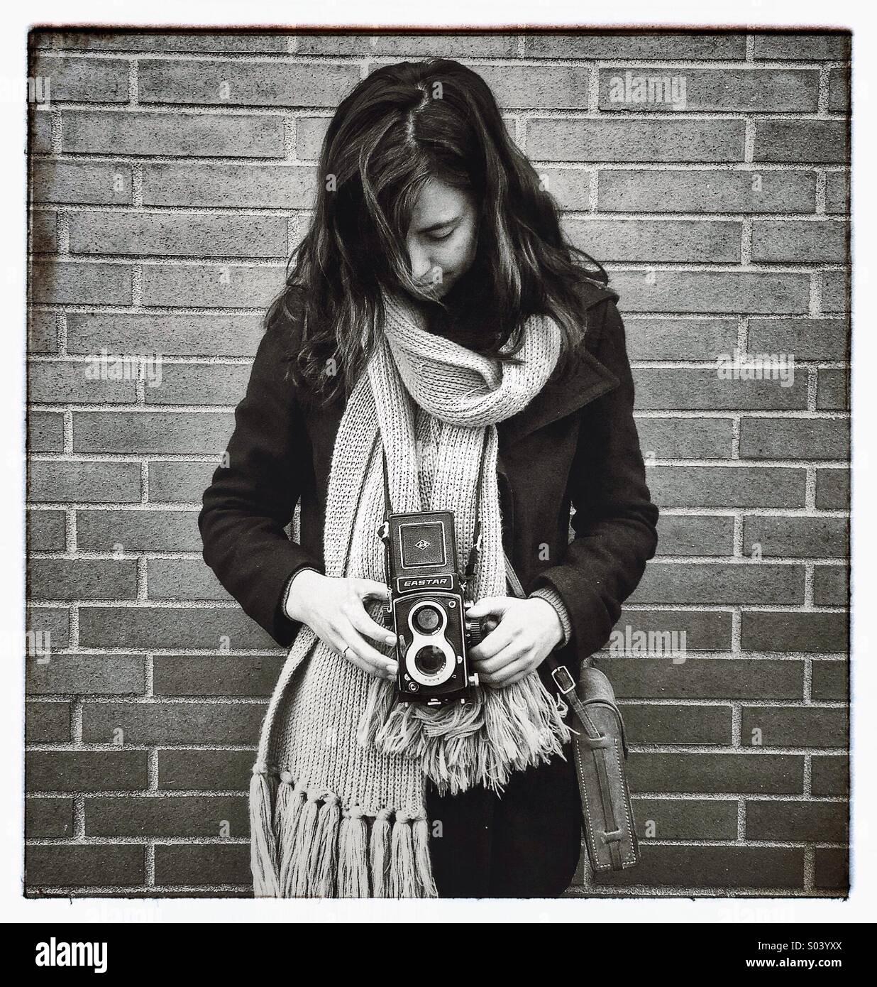 Mujer joven tomar la fotografía con cámara vintage Imagen De Stock