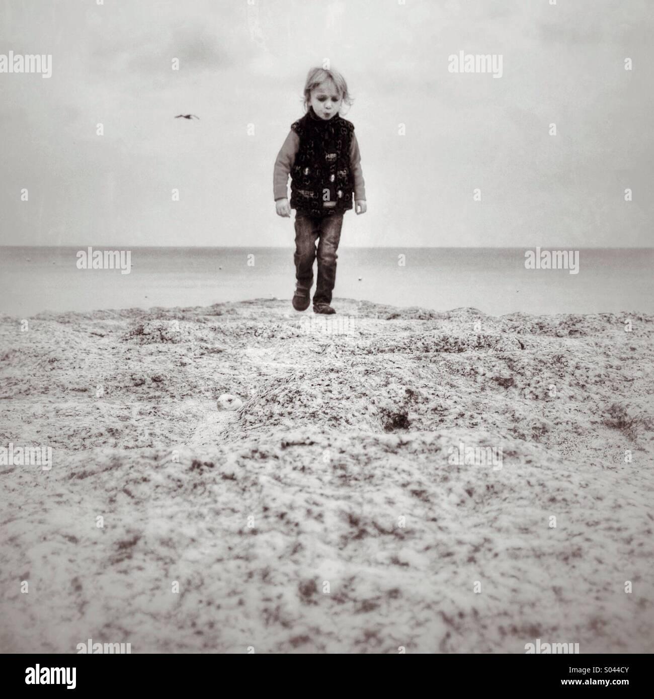 Niño sobre un camino de piedra por el mar en Dawlish Imagen De Stock