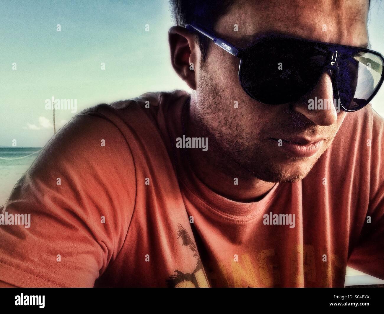 El hombre en la playa con camiseta naranja y gafas de sol, mirando pensativo, Dj Imagen De Stock