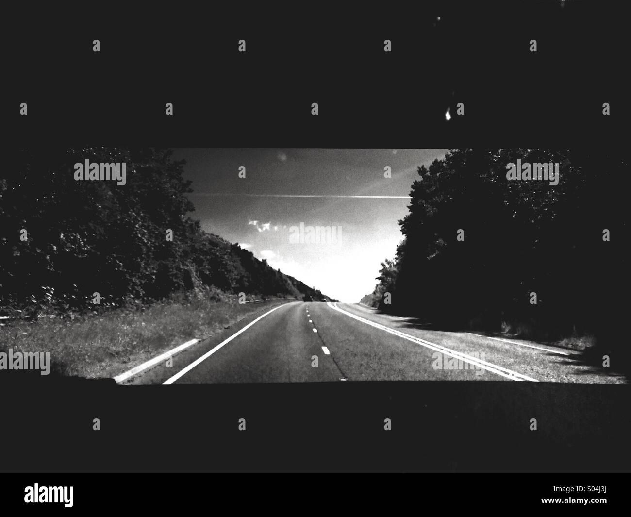 Ver a través del parabrisas de un vehículo en movimiento con un camino abierto en la distancia Foto de stock