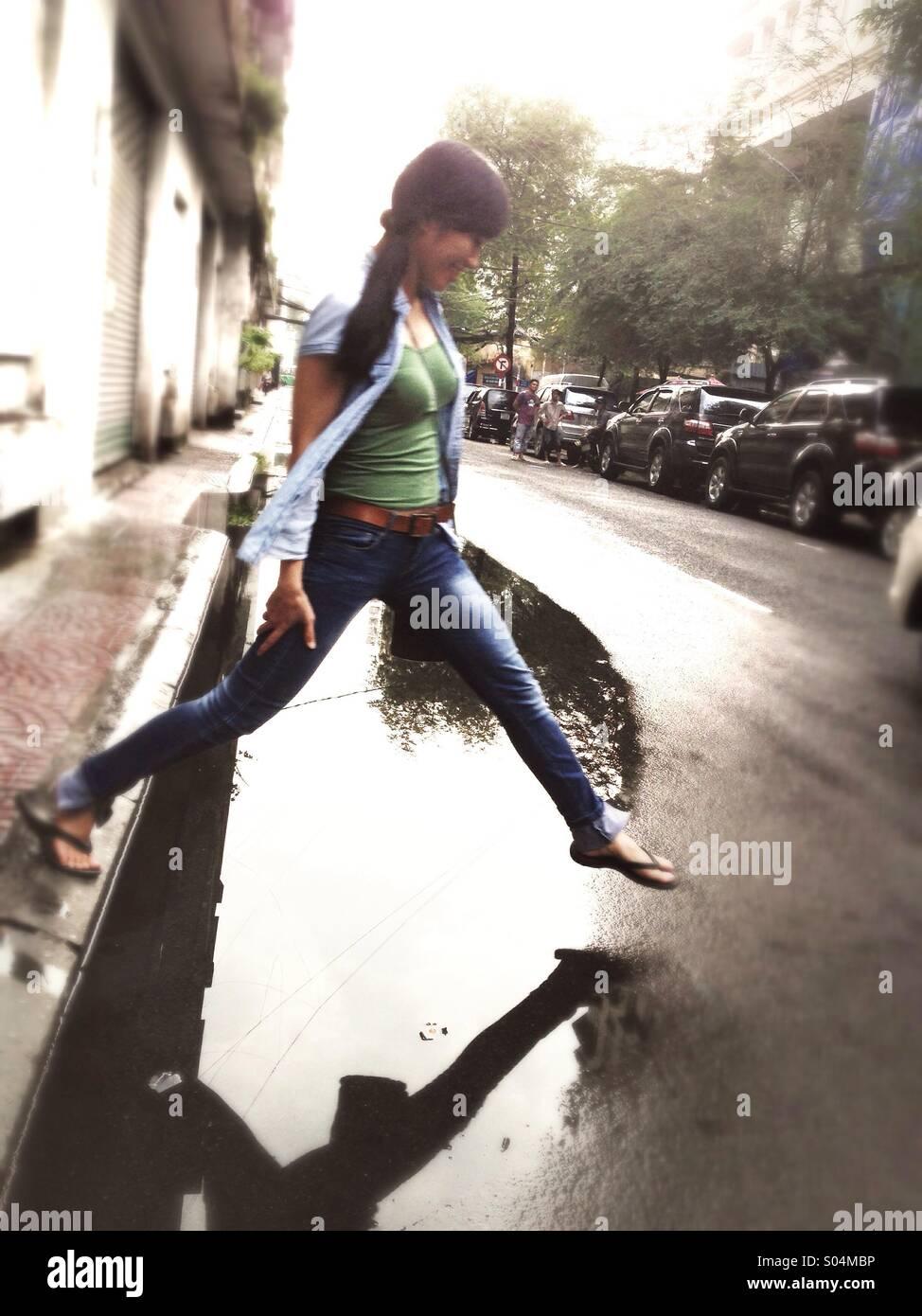Chica asiática, superando charco en Saigon, Ho Chi Minh, Vietnam Foto de stock