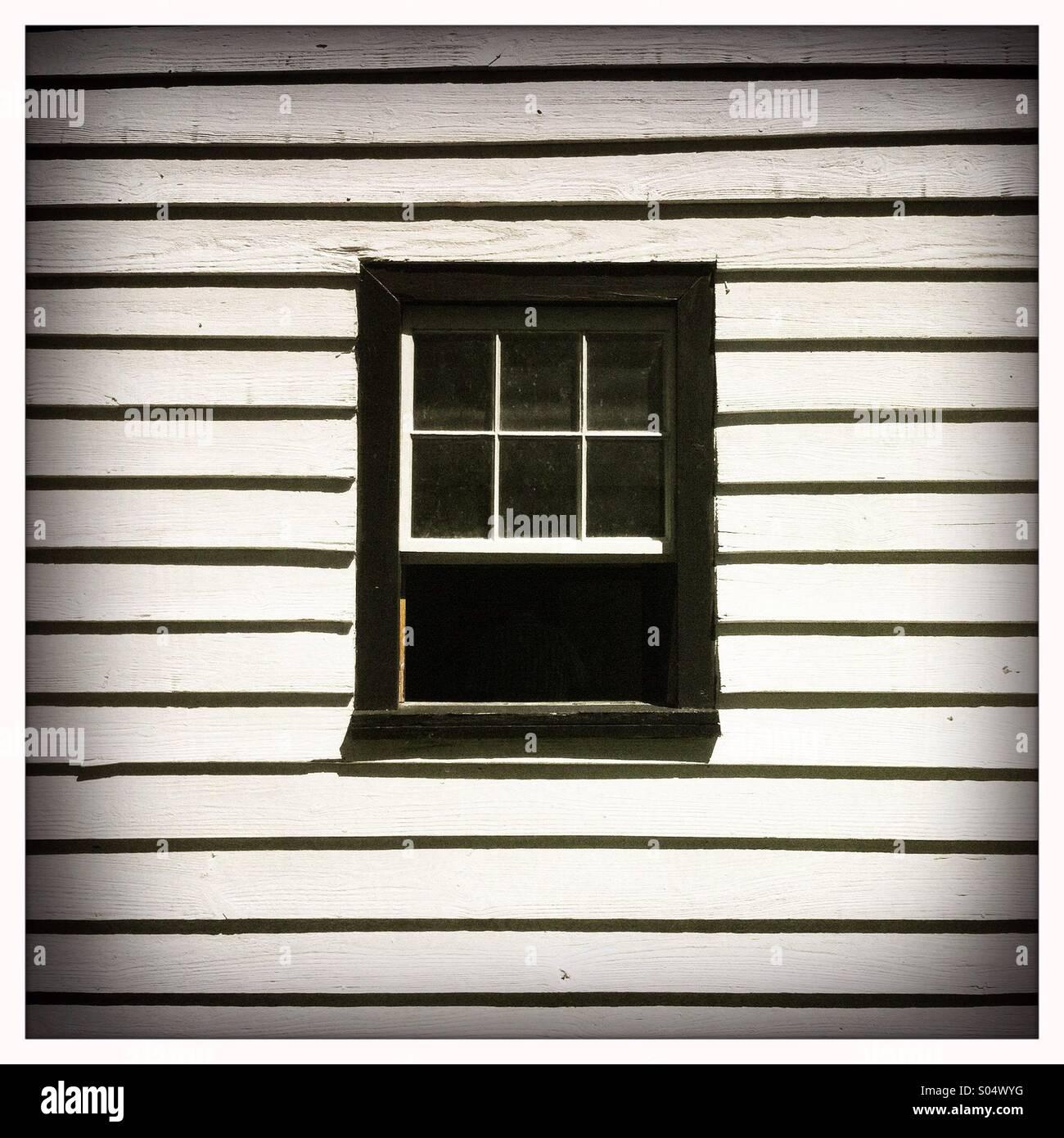 Una ventana negra casa enmarcada en una pared de madera blanca Imagen De Stock