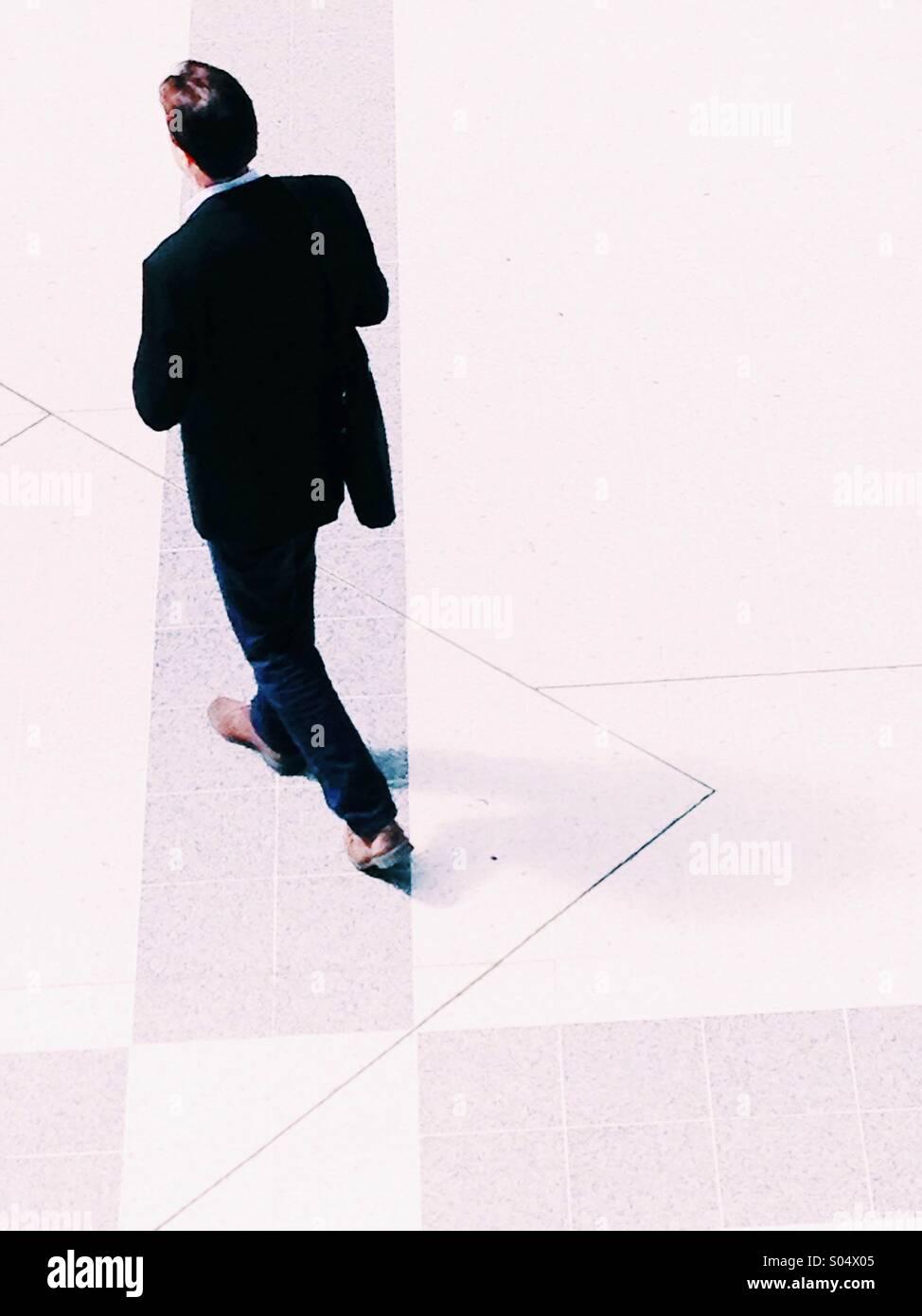 Empresario en un traje negro caminando visto desde arriba Imagen De Stock