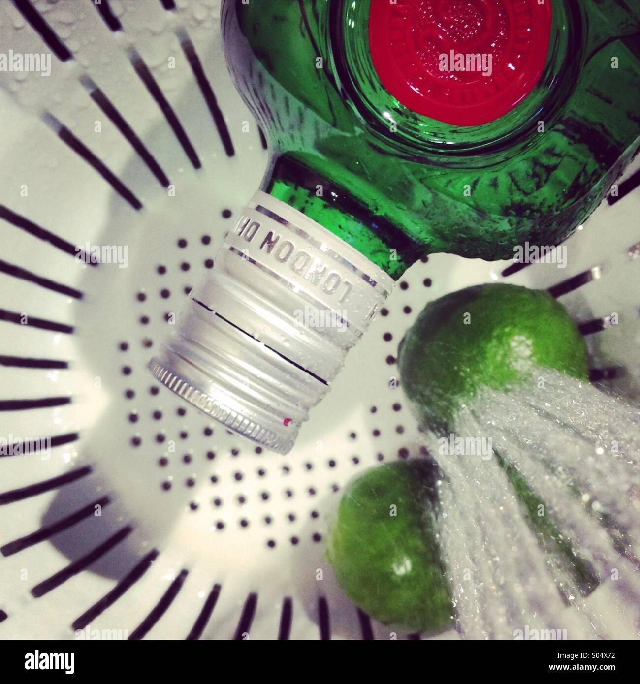 Verde botella de gin junto al limes de lavado con un chorro de agua si mientras está sentado en un colador. Imagen De Stock
