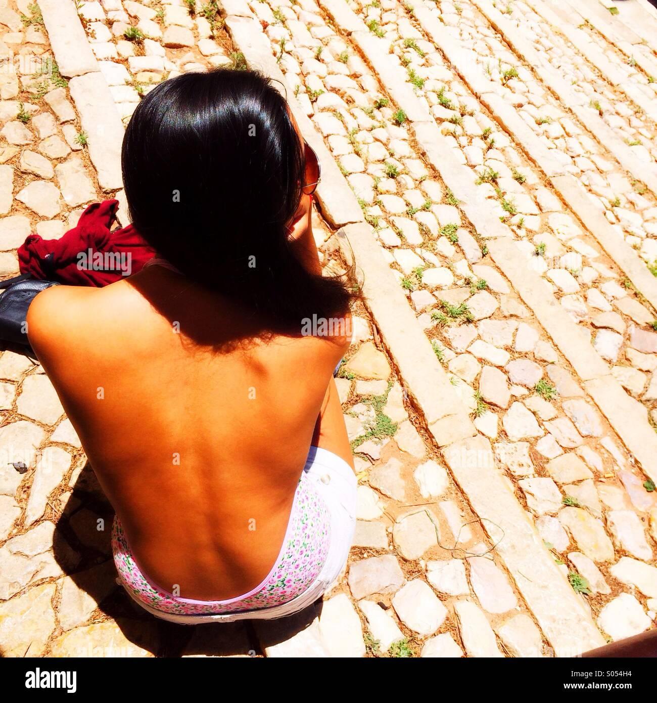 Chica sentada en escalones de piedra, Portugal Imagen De Stock