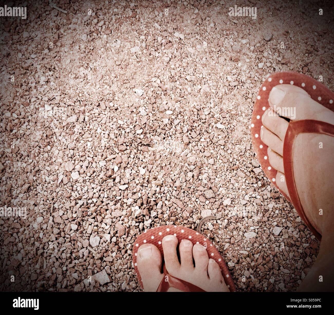 Pies con flipflops rojo sobre arena. Foto de stock