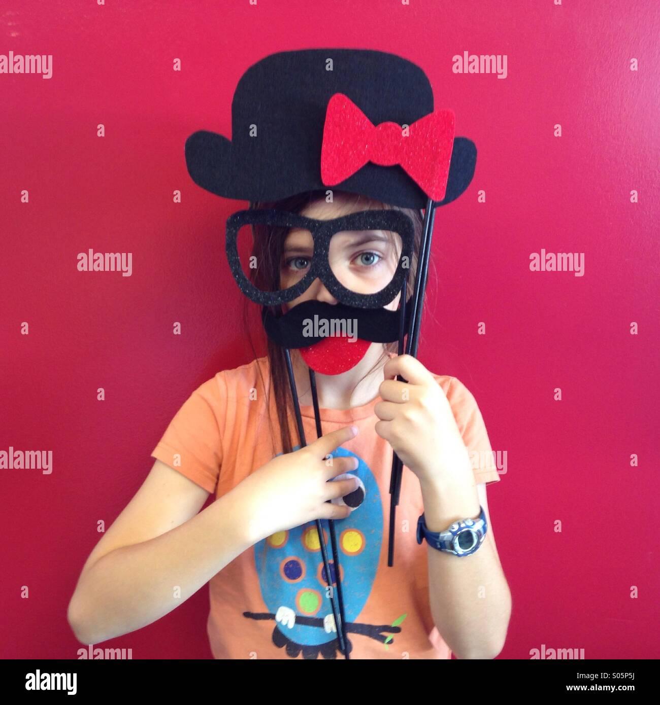Silly kid lleva gafas y un bigote falso contra una pared roja. Imagen De Stock