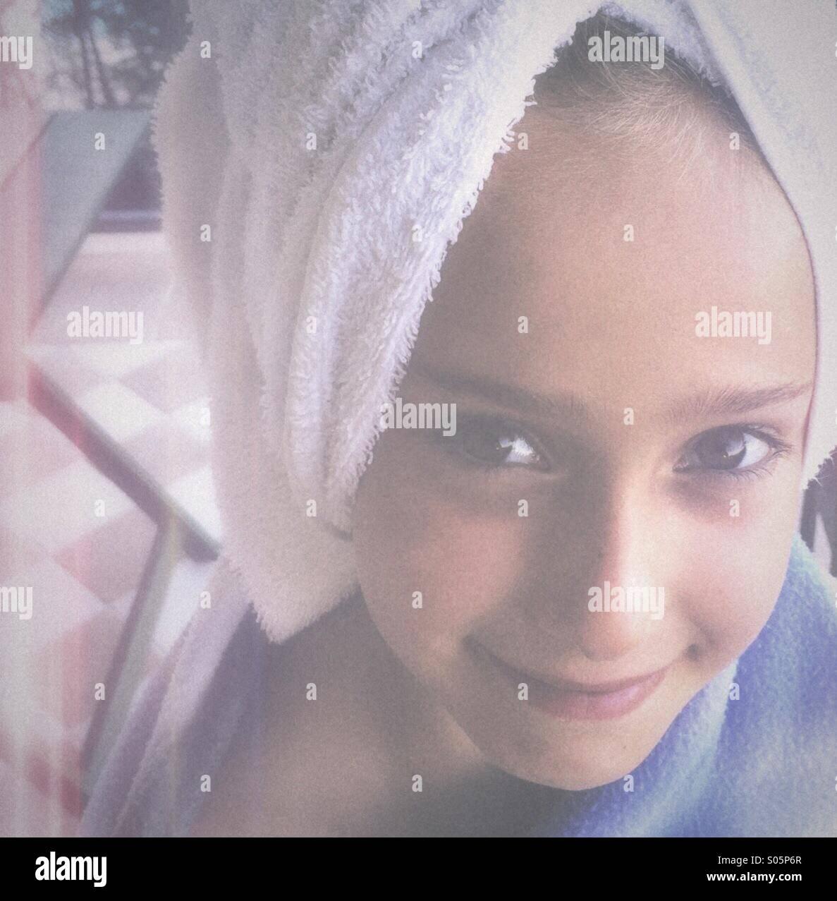 Chica con una toalla sobre su cabeza sonriente Imagen De Stock