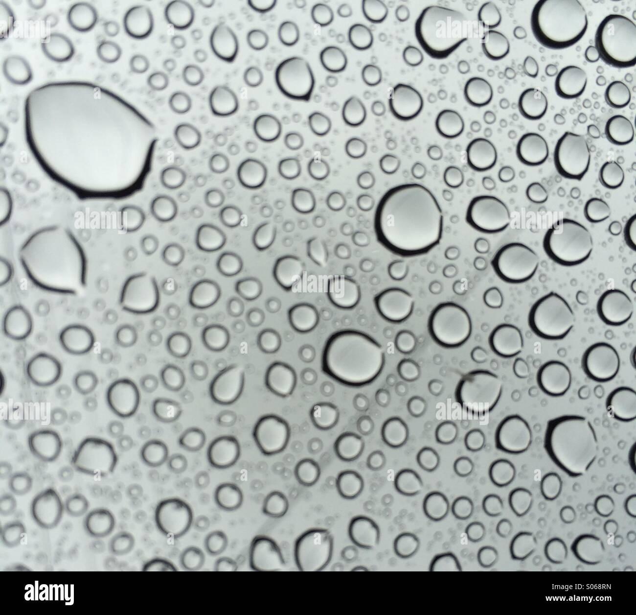 Techo solar de Seattle. Mirar a través de las gotas de lluvia al cielo gris de verano. Imagen De Stock