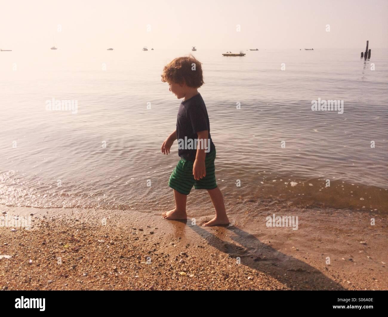 Un chico jugando en una playa soleada durante el verano en Connecticut, EE.UU. Imagen De Stock