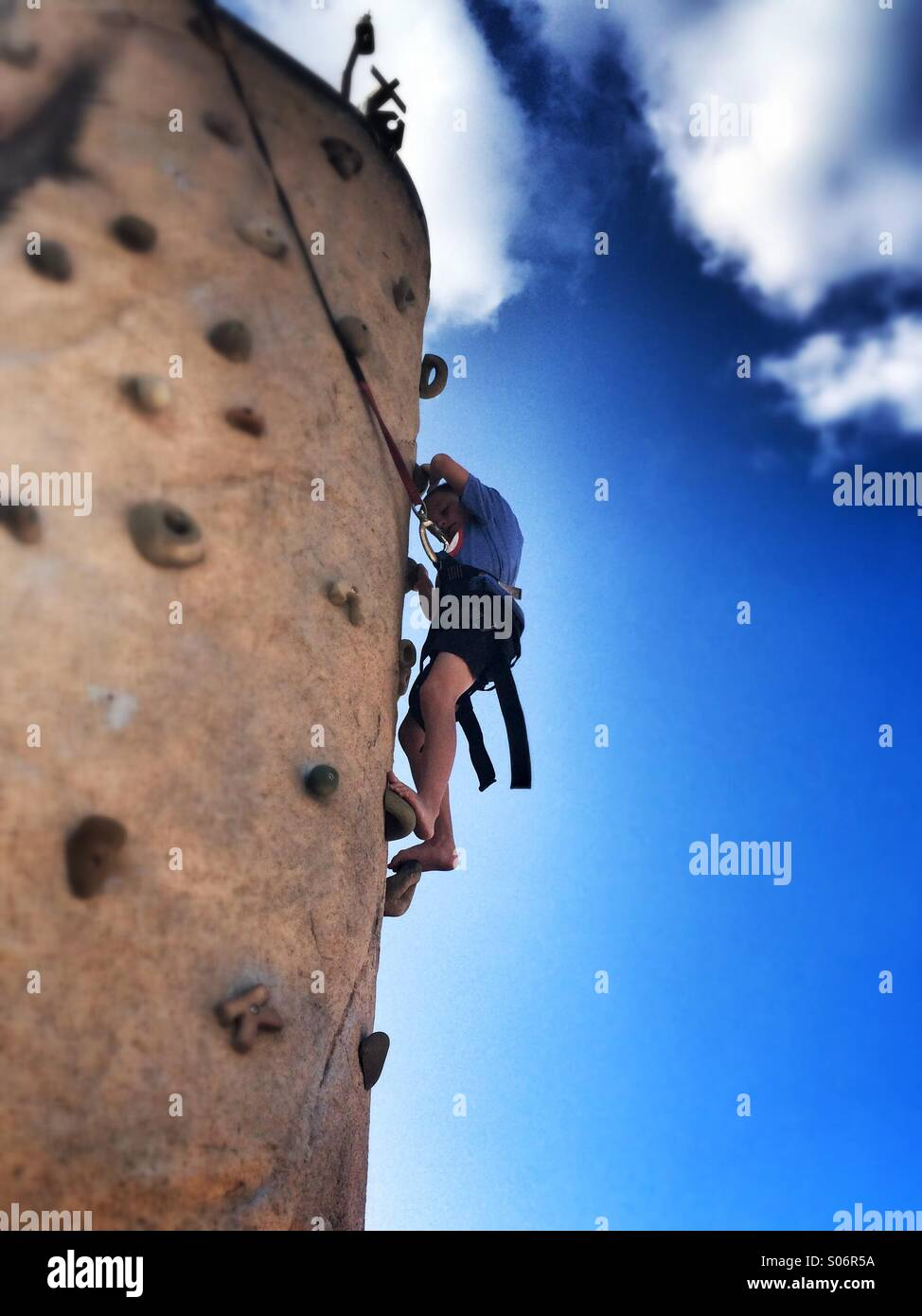 Un joven intenta trepar por una pared de roca Imagen De Stock