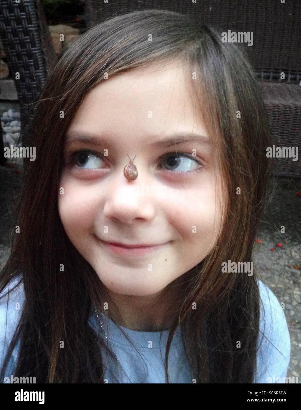 Una joven chica encantadora Sonrisas con un pequeño caracol en su nariz. Imagen De Stock