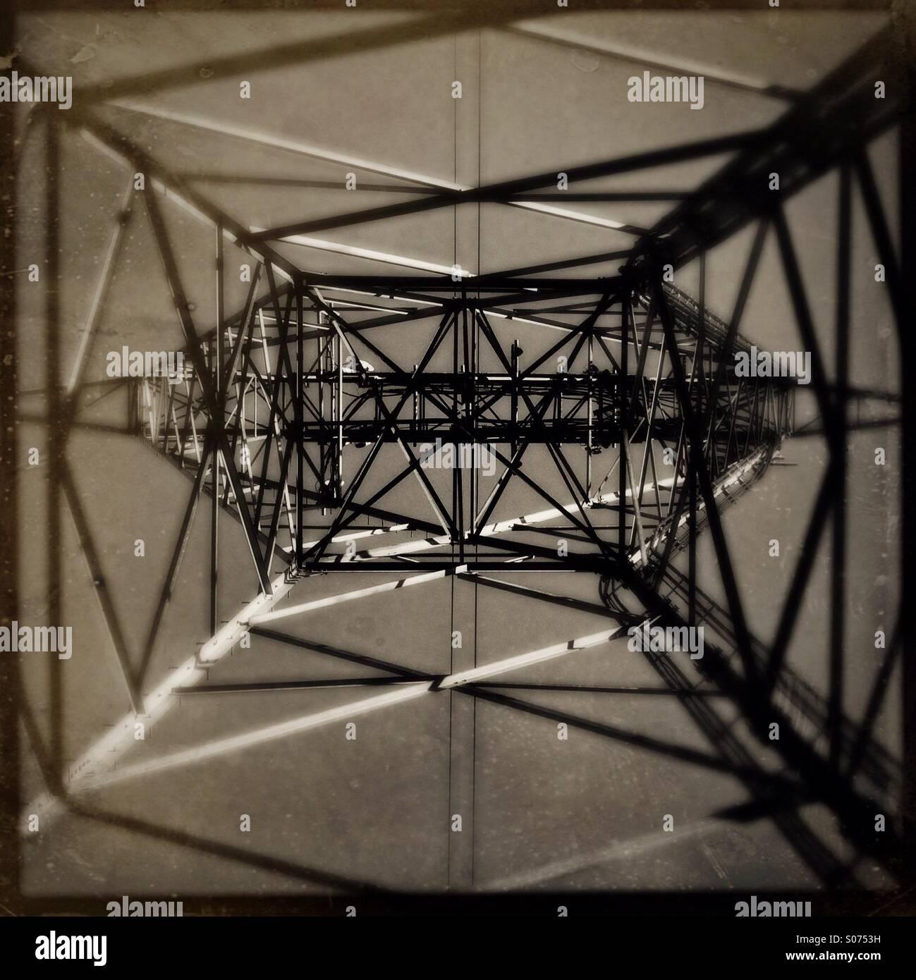 Mirando hacia arriba desde el interior de una torre eléctrica de metal. Imagen De Stock