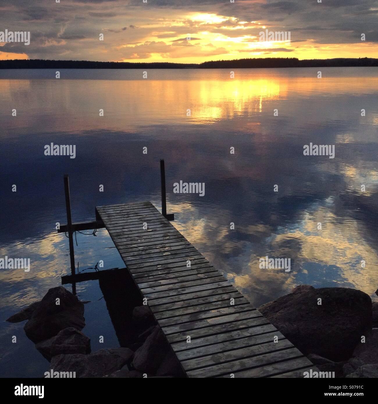 Medianoche Arctic Sun sobre un lago finlandés todavía en una casa de veraneo, como nórdico Imagen De Stock