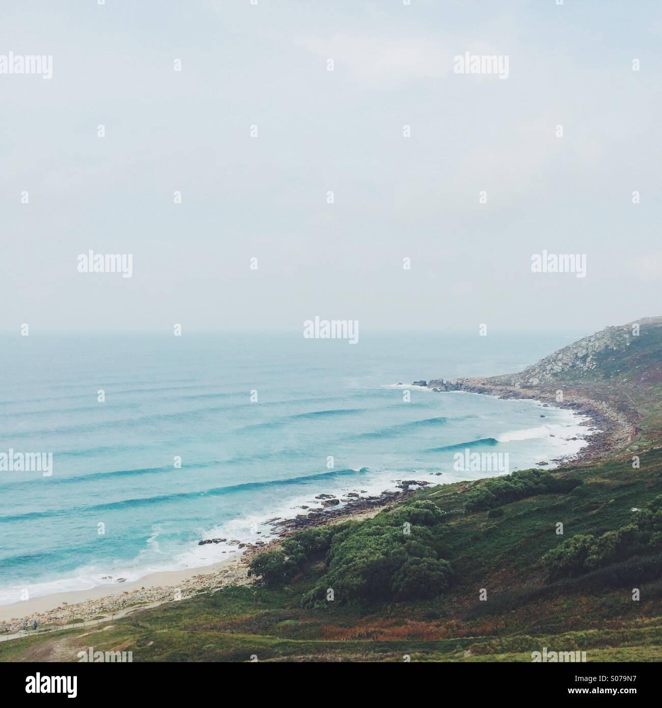 Las olas rodando en una orilla rocosa y cabecera. Imagen De Stock