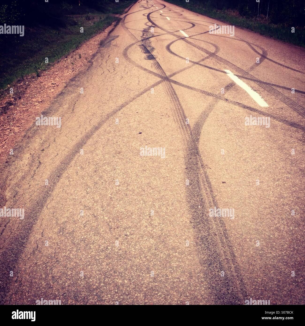 Marcas de neumáticos de entramado de derrape y burn-off en un tradicional Nordic red road Imagen De Stock