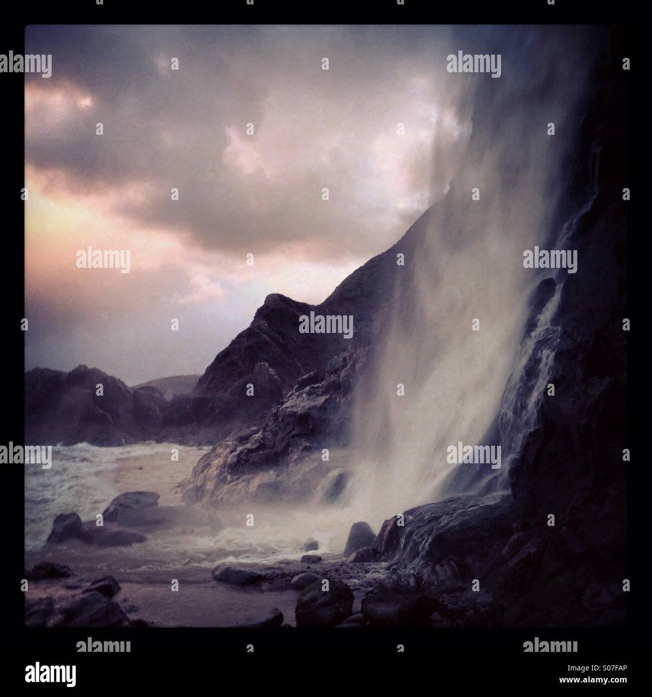Una cascada en los acantilados junto a la aldea de Tresaith, Wales, REINO UNIDO Imagen De Stock