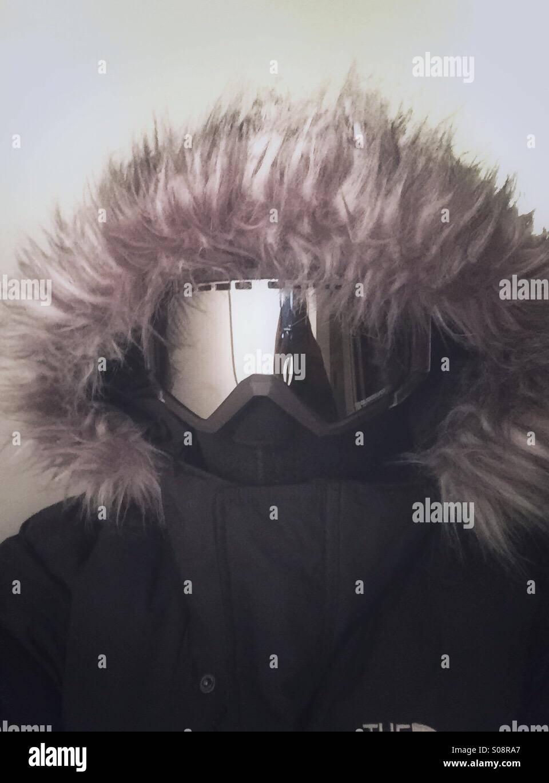 Un chico vistiendo abrigo de pieles con una capucha, pasamontañas y gafas de esquí Imagen De Stock