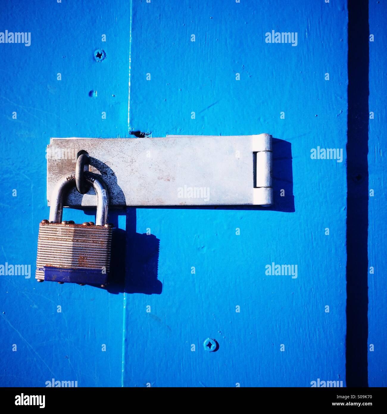 Un candado cerrado en una puerta de madera azul. Foto de stock