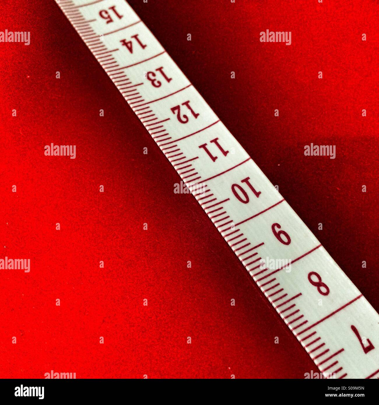 Cinta métrica mostrando centímetros sobre un fondo rojo. Imagen De Stock