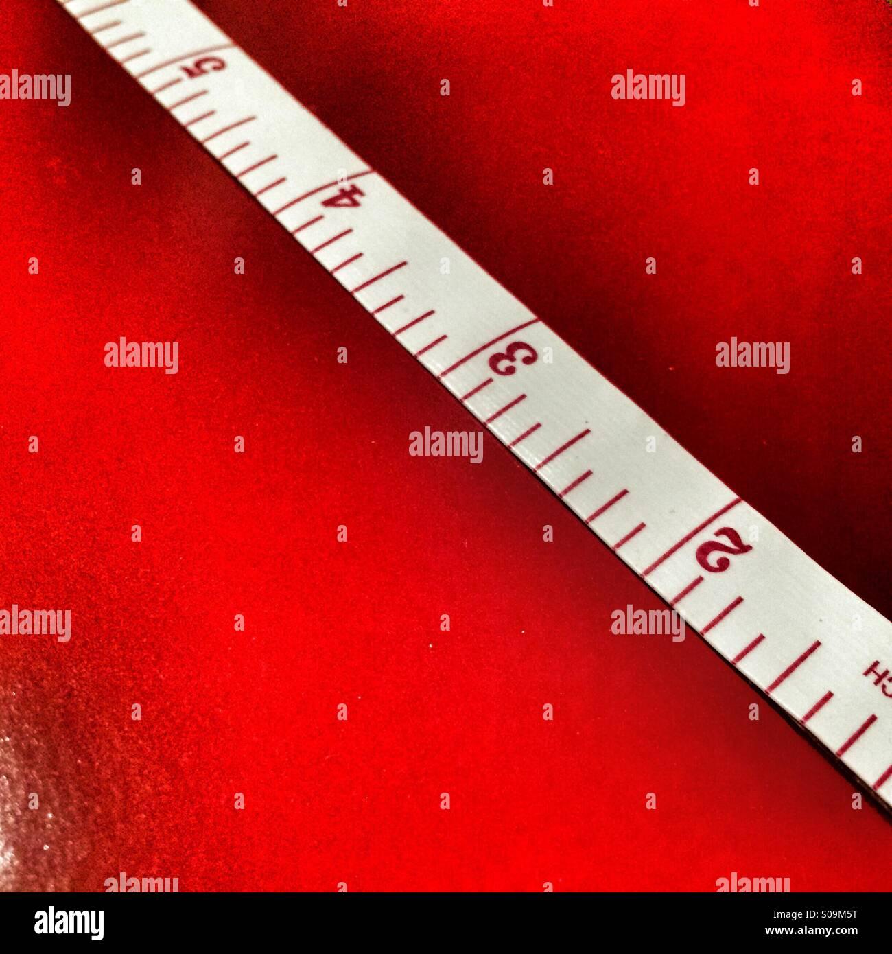 Cinta métrica mostrando pulgadas sobre un fondo rojo. Imagen De Stock
